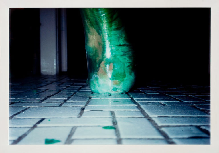 A photograph shot at ground level captures an extreme close-up of a heel and ankle from behind. Enclosed in a clear latex balloon filled with viscous green liquid that distorts its shape, the foot rests upon a floor of tiny, square, white tiles, like those used in bathrooms.