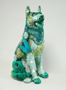 A mass-produced, ceramic German shepherd sits upright and alert with mouth open and tongue extended as if panting. Panels of elaborate hand-crafted crochet in shades of mint, citron, and emerald green form a skin-tight web that entirely envelops the dog.