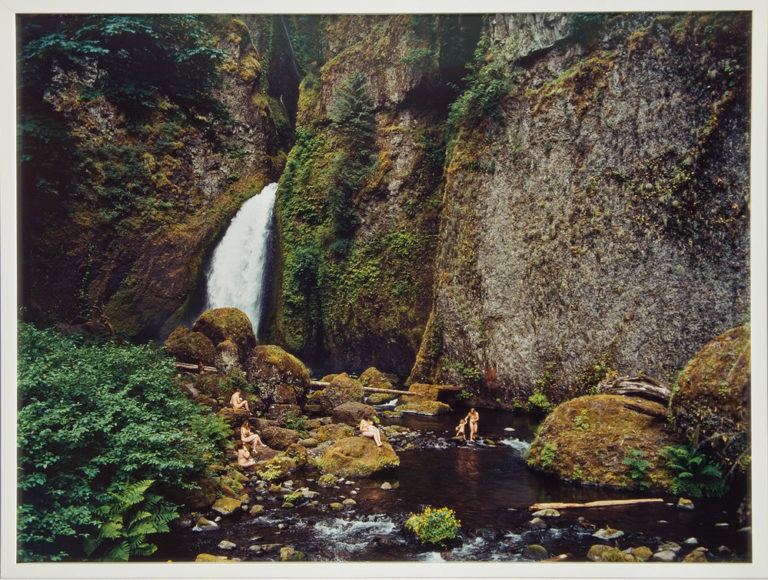 Photograph of a splendid landscape scene featuring a cliff, waterfall and stream. Nude mothers with their children sit on rocks or play in the stream. The human figures are dwarfed by blocks of green foliage in the lower left corner and walls of steep rock covered subtly by moss.