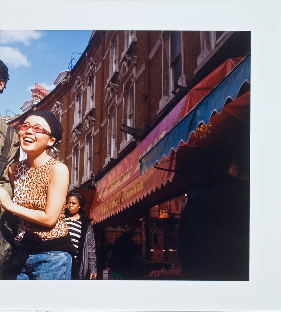 Color photograph of a street scene. Red brick buildings with colorful awnings are on the right and a smiling woman on the left. She holds the arm of a companion who has been cropped out of the left side of the image.