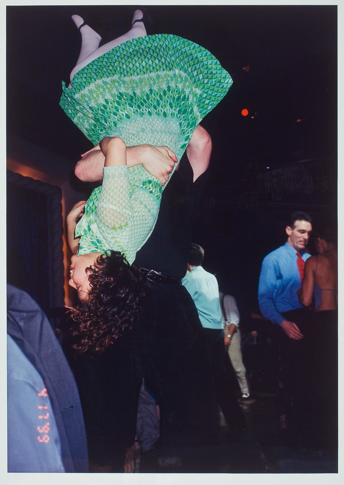 Color photograph of a woman in a green dress being flipped upside down by her dance partner dressed in black. Other couples are dancing in the background.
