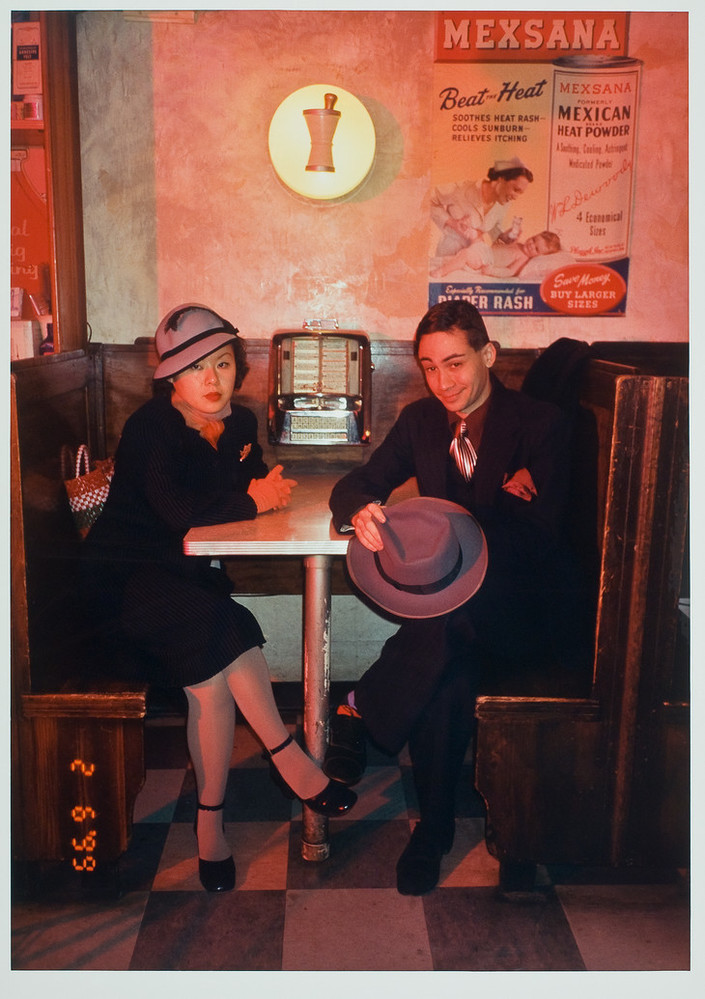Color photograph of a man and woman sitting at a diner booth, looking at viewer. Woman on left wears gray hat with black trim. Man on right wears a dark suit and shiny silver tie. He holds his gray hat in his hands. Behind them on the table is a small juke box.