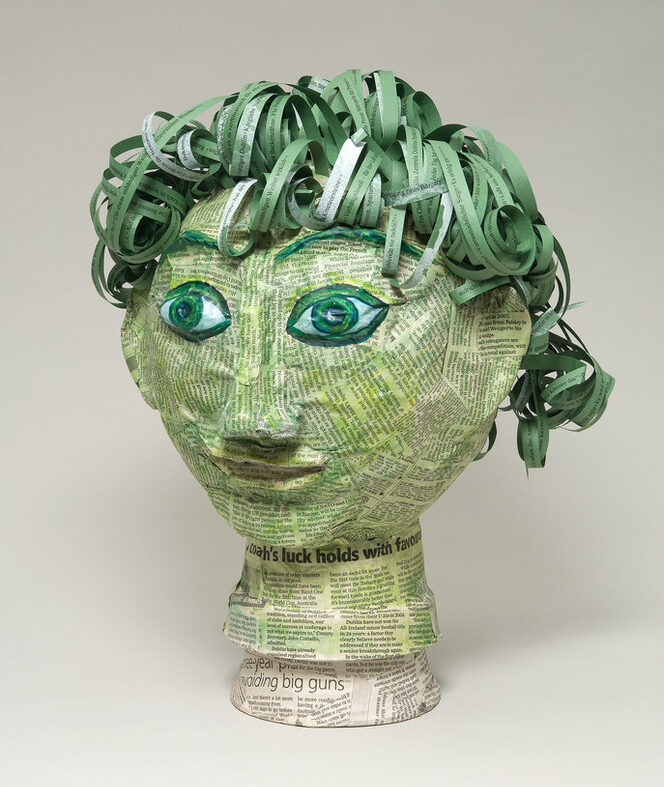 Papier-mâché head covered in clippings of pages from James Joyce's novel Ulysses. In varying shades of green, the head includes curly, lettered strips for hair and wide and classic-Greek-style eyes under arched eyebrows.