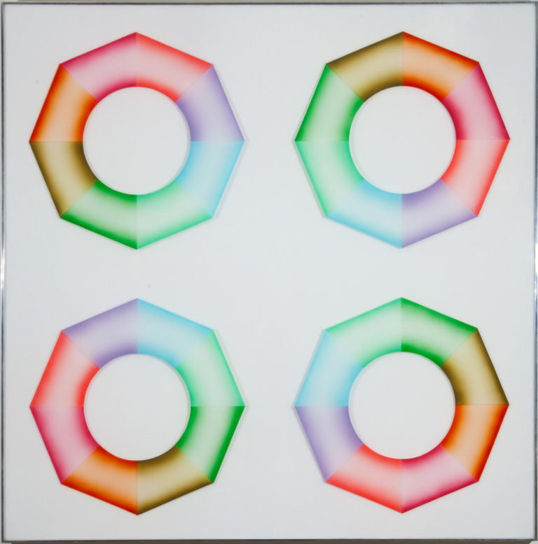 Four hard-edged octagonal rings, divided into wedges of brown, orange, pink, red, purple, blue, mint green, and grass green, sit on a square, white surface. Dark at the inner and outer edges and light in the center, the colors create the illusion of curved 3-dimensional objects.