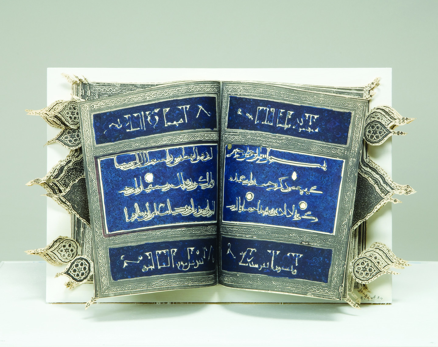 An open book with Arabic text on a dark blue background divided into horizontal sections by decorative silver border. Cut-out arabesques extend out beyond the edge of the book to the right and left.