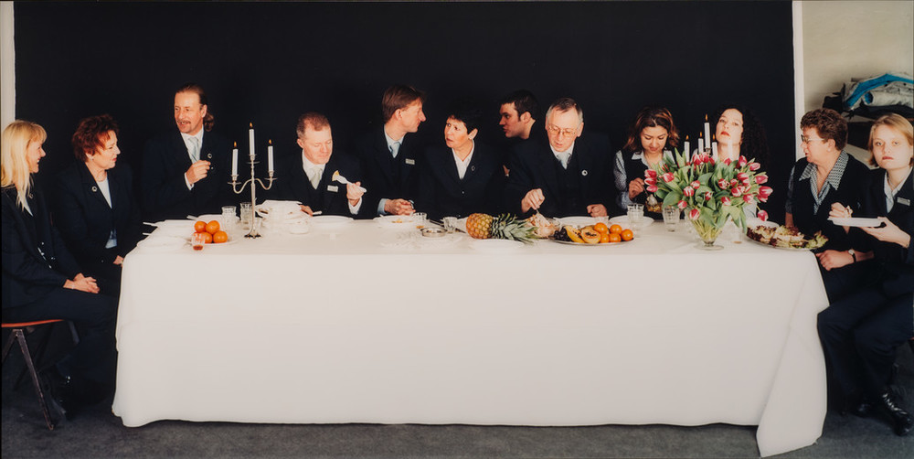 Twelve light-skinned men and women in dark suits sit on the ends and far side of rectangular table situated horizontally to the viewer. Covered with a white cloth, the table holds 2 candelabra, a flower bouquet, and assorted fruit. The people eat, chat, or look out at viewers.