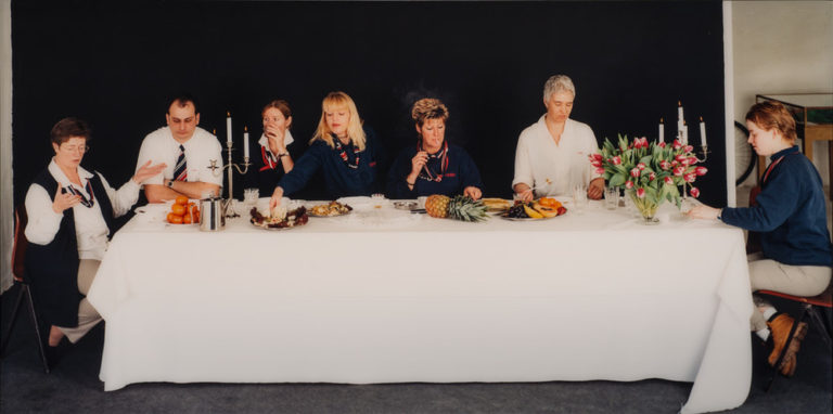 In front of a black background, seven light-skinned, plainly dressed women and men sit around a rectangular table. Food, candles and tulips sit on the white table cloth. The women and men gesture, smoke, drink, and eat, but do not engage with each other or the viewer.