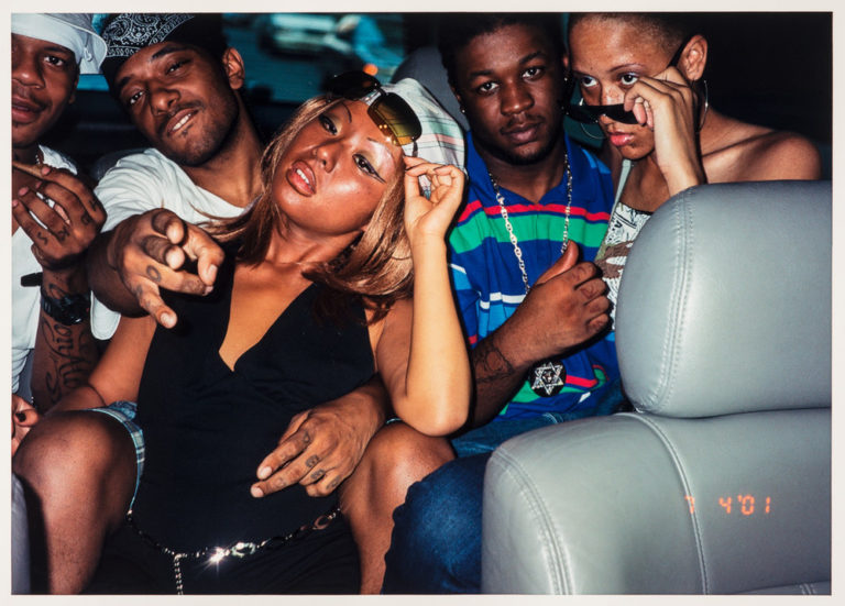 A color photograph of five people, three medium-dark skinned and two medium-light skinned. They are sitting in the backseat of a car. To the right is the gray front seat on top of which is an orange time stamp,