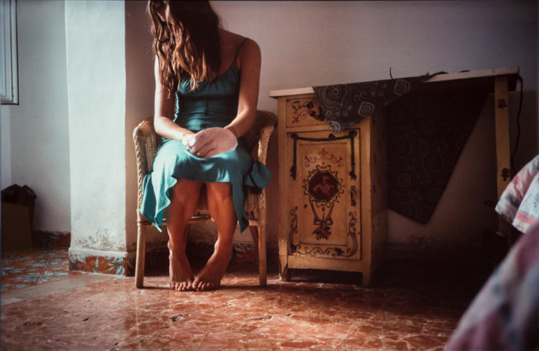 A photograph portrays a woman clad in an aqua blue slip dress. She sits in a wicker chair in a naturally lit room with red marble flooring. Her head and shoulders slump forward so that her long brown hair obscures her face. A water-filled latex balloon encloses her left hand.