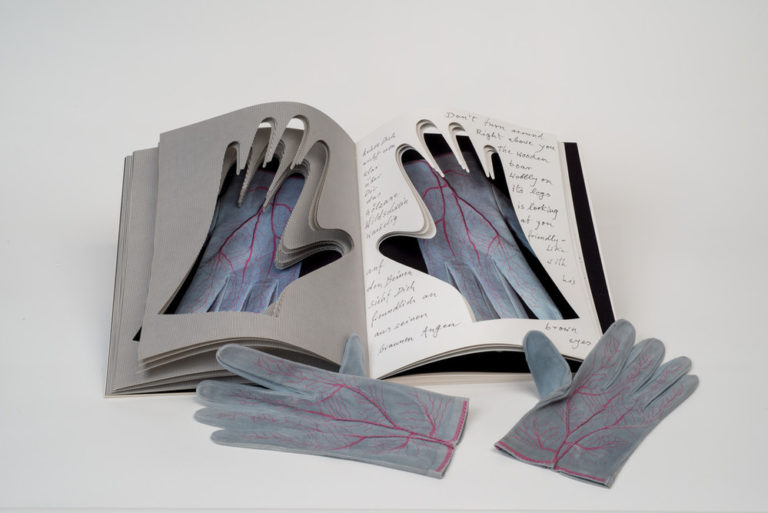 An open book into whose pages the shapes of hands have been cut. Gray gloves painted with red veins are visible through the cutouts. An identical pair of gloves rest next to the book.