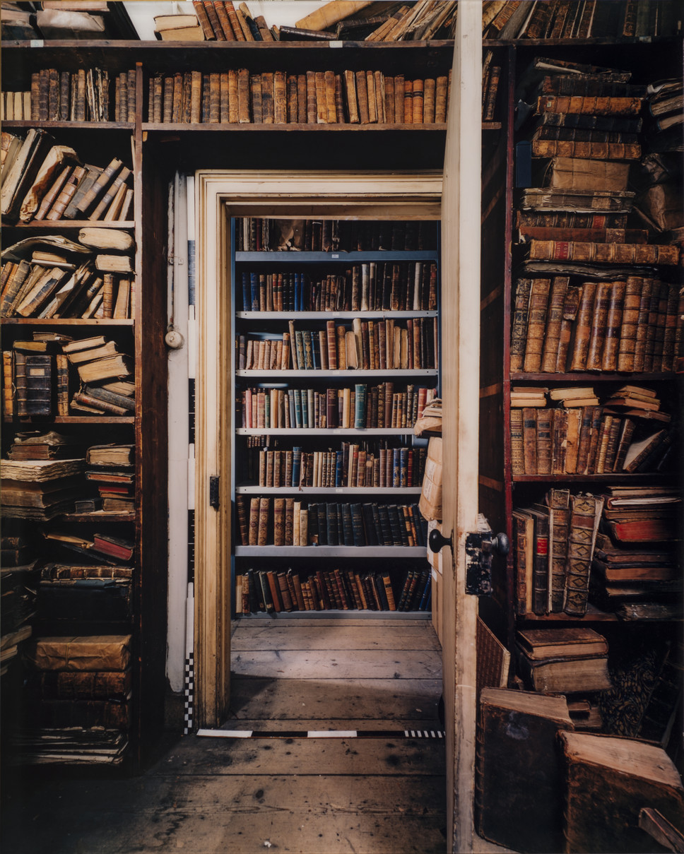 Color photograph of room with old books on bookshelves that stretch from floor to ceiling. In the center is an open door revealing another room with floor to ceiling shelves filled with books.