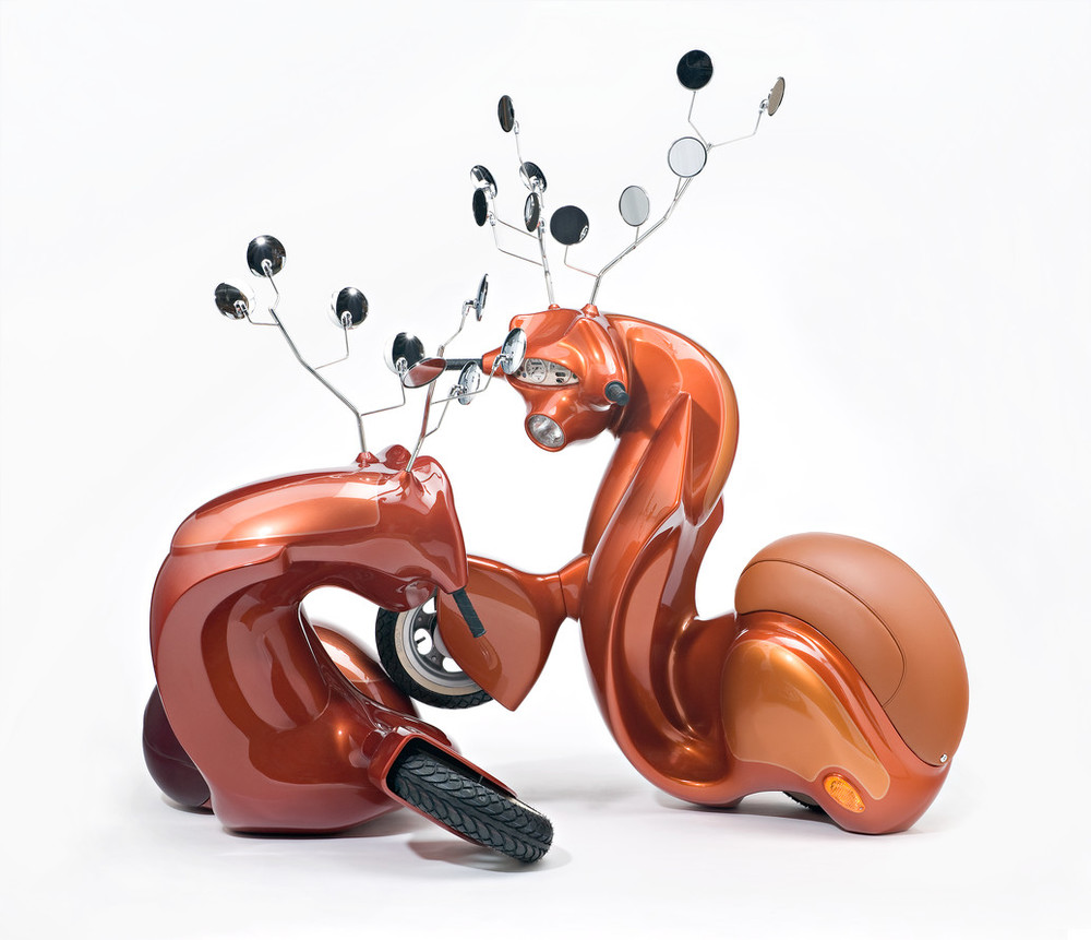 A sculpture consists of two metallic-orange motor scooters manipulated to resemble male deer. Leather seats become haunches, dashboard dials resemble faces, and multiple rear-view mirrors morph into antlers. The serpentine, hybrid animal-machines appear to spar for dominance.