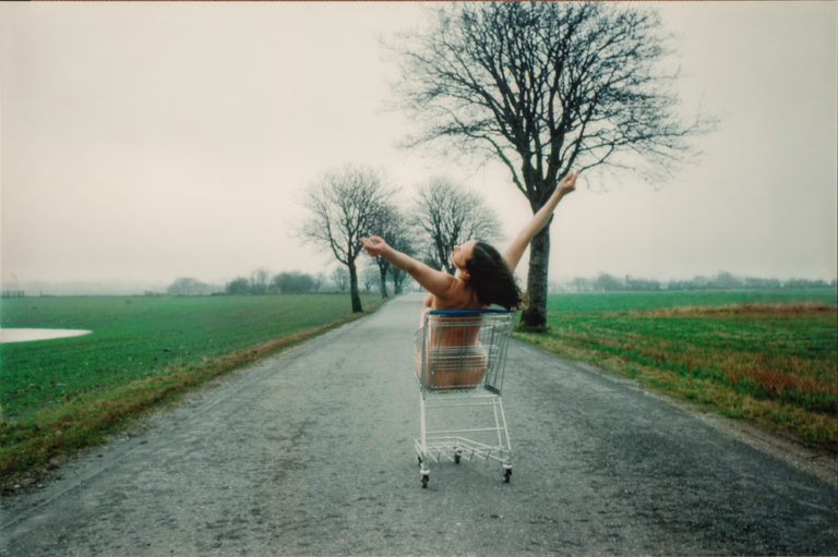 A photograph shows the nude artist sitting in a metal grocery cart. It is located on a paved road in a flat, empty landscape under a gray, misty sky. Her back to the viewer, the light-skinned, brunette woman holds her raised arms in a wide V-shape, suggesting joy or abandon.