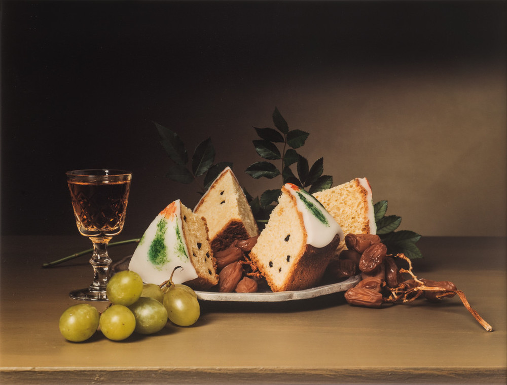 A full crystal sherry glass and plate mounded with raisins and iced cakes occupy the middle ground of a still-life photograph. Luscious green grapes sit in the left foreground, and greenery rises in the background. The image explicitly imitates18th-century, still-life paintings.