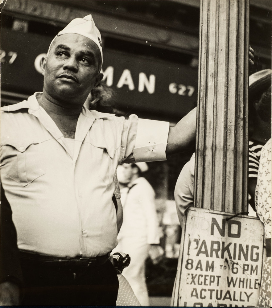 Candid street-scene photograph of a dark-skinned man wearing a WWII era military uniform. He gazes up and the his left, his left arm raised as he casually holds on to a lamp post with a