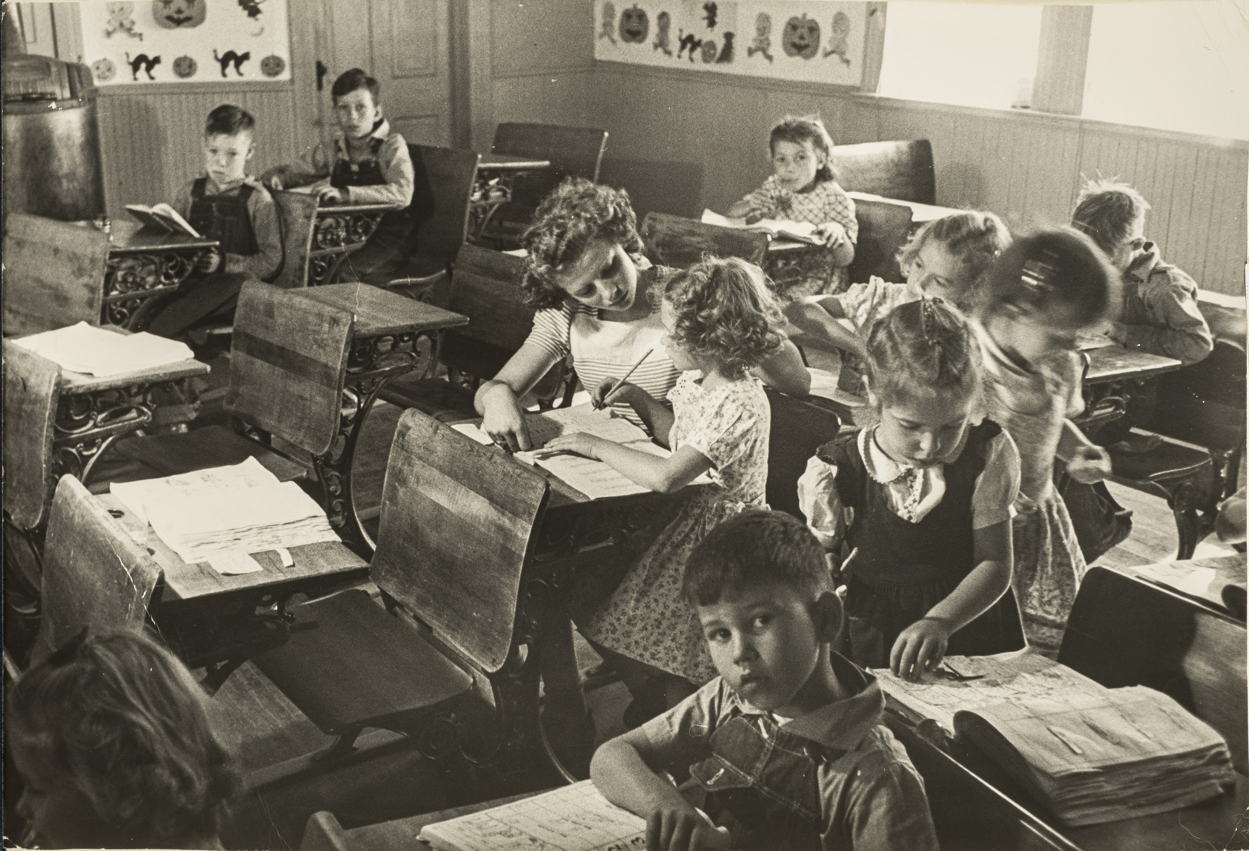 Black and white photograph of a primary school classroom in 1948. Light-skinned children sit at dark wood desks attending to books and papers or looking directly into the camera. At the center, the young teacher assists a girl with her lesson.