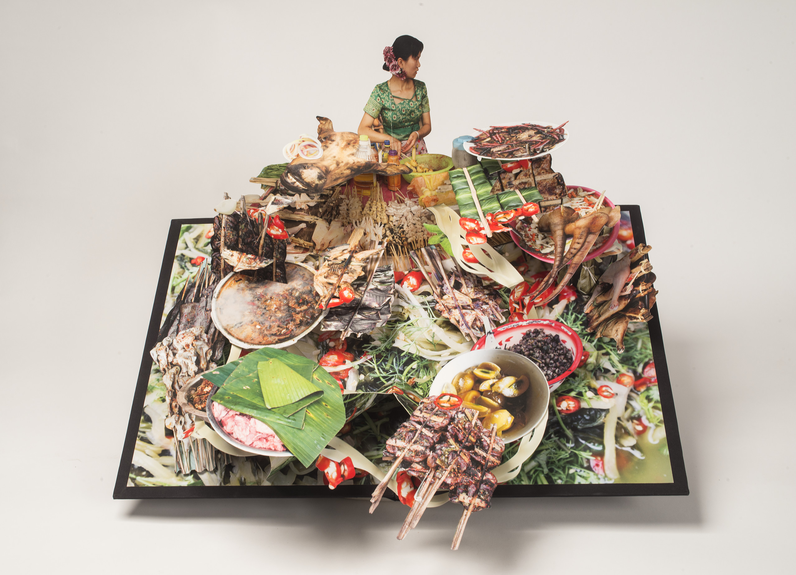 Large-scale pop-up book with a dark haired woman behind a huge display of food. She wears a green dress and purple flowers in her hair and turns to look over her left shoulder. The food explodes forward with bowls of soup, skewered meat, banana leaves, pig tail, and more.