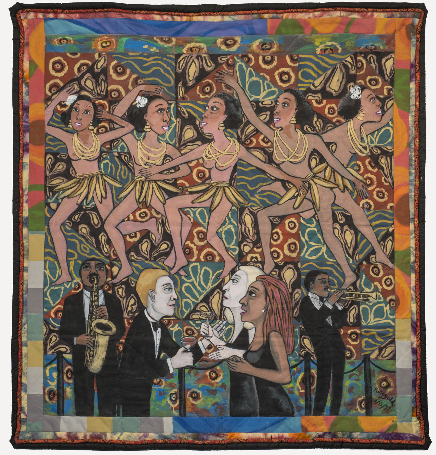 Colorful quilt with a multi-patterned background that depicts five medium skin toned, bare breasted dancing women wearing skirts of bananas and yellow necklaces. Below, from left to right, a medium-dark skin toned and light skin toned men and women interact and play brass instruments.