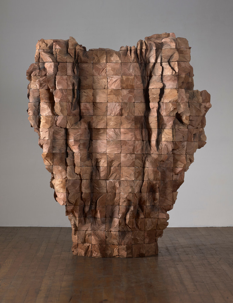 An abstract wooden sculpture composed of four-by-four beams of cedar stacked and roughly carved. Wide at the top, it tapers towards the bottom and sits directly on the floor.