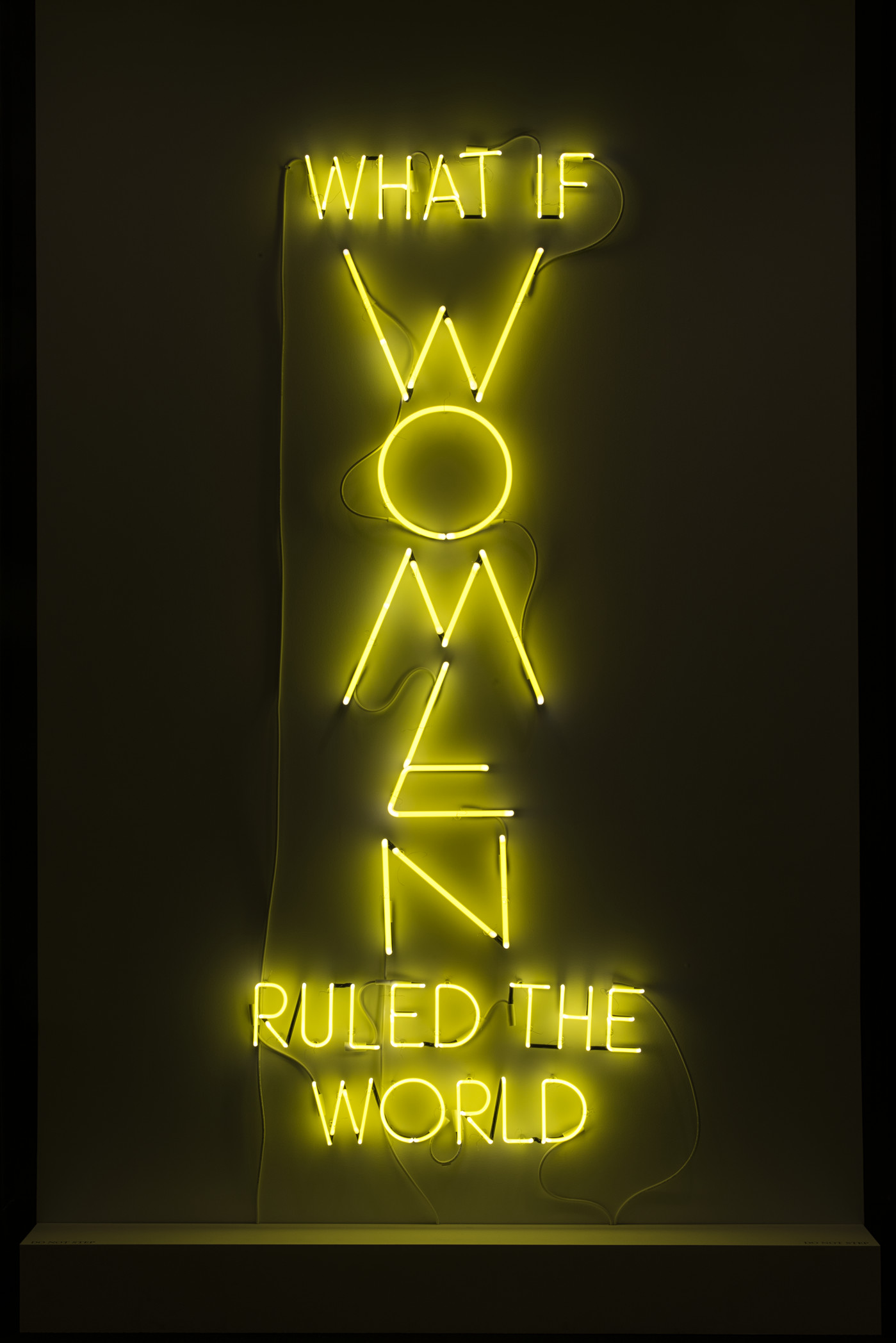 "The phrase 'What if Women Ruled the World' is sculpted with neon tubes of bright yellow, in all capital letters. The letters of ""WOMEN"" are larger than the rest and are configured vertically."