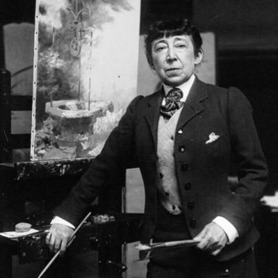 Black-and-white photograph of a light-skinned older woman with dark hair and bangs. She wears a dark suit with light-color vest, white collared shirt, and stripped necktie. She holds brushes in both hands and leans against an easel. Behind her is an unfinished painting.