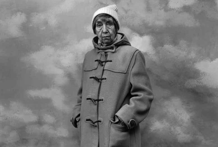 A black-and-white photograph of a light-skinned adult older woman wearing a long winter coat and white knitted cap. She has short hair and stands against a backdrop resembling a cloudy sky with her hands in her pockets.