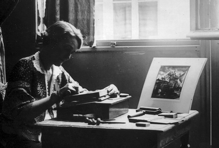 A black-and-white photograph of a woman seated at a table by a window. Her face, in profile, is in shadow. She looks down at a wood engraving. One hand steadies her woodblock while the other carves. Engraving and printing tools are scattered on the table, along with a small print.