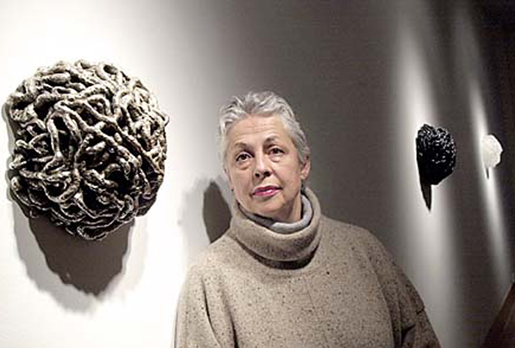A light-skinned adult woman with short, grey hair. She gazes directly into the camera with a frank expression, her eyebrows slightly raised. On the wall next to her hang three round sculptures of grey, black and white. They are masses of coils and resemble rounded brains.