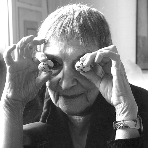 Close-up black and white photo of an older woman with light skin and cropped hair. She holds up two small, speckled eggs to her eyes, the right one just visible. She sits in a bright, sun-lit room, a window on her right and wears a dark blazer and wrist watch.