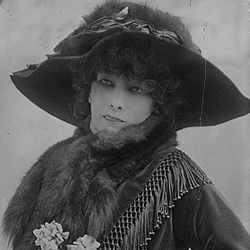 Black-and-white photo of a light-skinned adult woman with dark curls. Starring off-camera, she wears a large dark hat, a dark dress with long sleeves, and fur stole. Her mouth opens slightly, showing her top row of teeth, and she holds a bouquet, visible at the bottom of the frame.