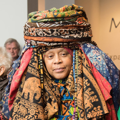 A medium skin-toned adult woman smiles with only her face visible from underneath an elaborate headwrap of nearly a dozen different colorfully printed fabrics. The wrap is piled like a turbin atop her head with fabric cascading down to surround her face.