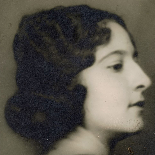 Soft-focus black-and-white studio portrait of the head of a light-skinned young adult woman in profile. Her curly dark hair is pulled back in a low bun.