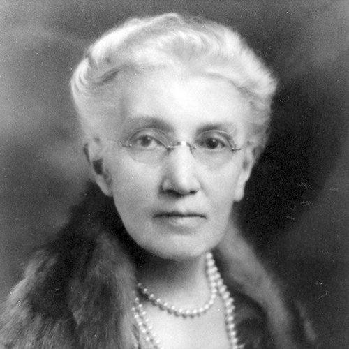 A black-and-white soft-focus studio portrait photograph of an older light-skinned woman with white hair pulled back. She wears rimless glasses, three strands of pearls around her neck, and a fur wrap over her shoulders.