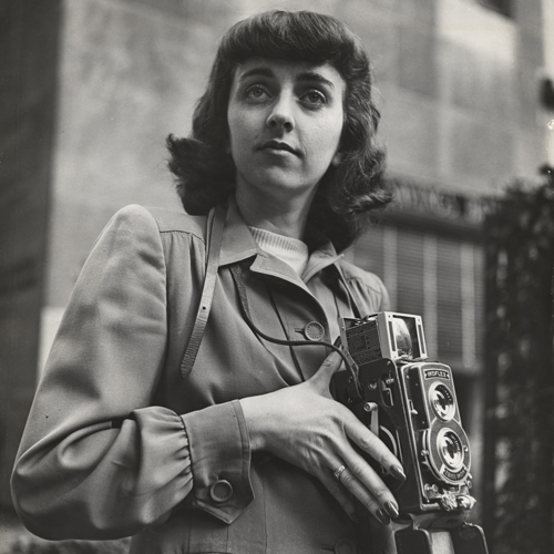 A black-and-white photograph of a light-skinned young woman with medium-length dark hair and thick bangs. She is depicted standing outdoors in front of a building. She wears a coat and holds a large camera.