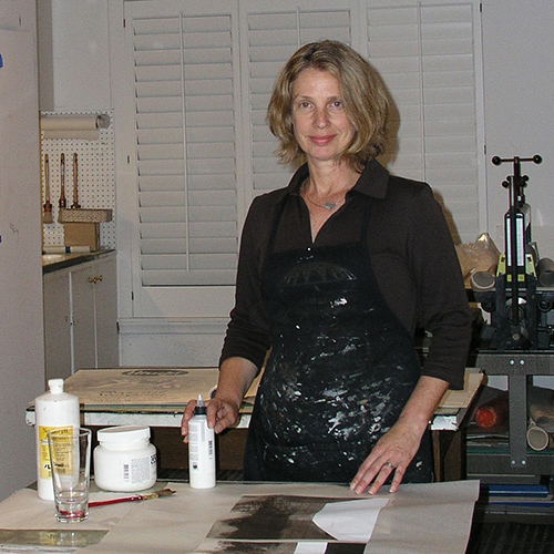 A light-skinned adult woman with shoulder length blond hair. She wears a paint covered apron and stands behind a tablle covered in art supplies, incluidng brushes and photographs. She smiles slightly, her hands posed as if they were about to begin creating.