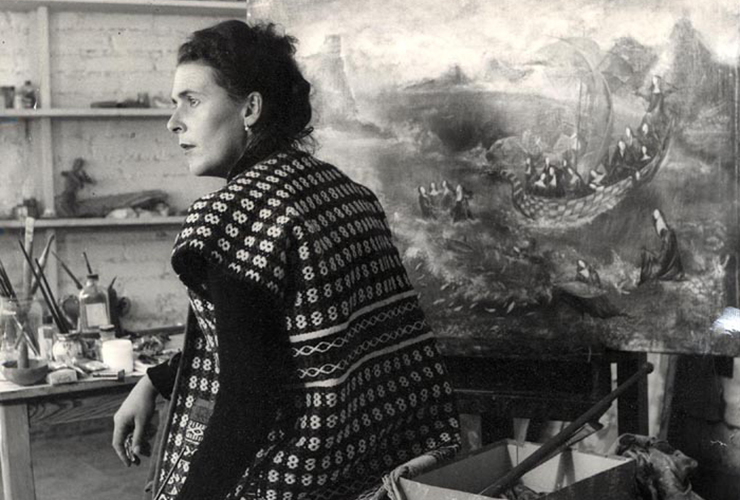 Black-and-white photograph of a light-skinned adult woman with dark curly hair. She sits with her back to the viewer, looking over her left shoulder, her face in profile, surrounded by art supplies. A painting of nuns in a boat on rough seas sits on an easel in front of her.