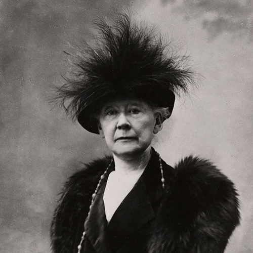 Black-and-white photograph of a seated older woman with light skin. She wears a dark dress with a fur stole and long necklace. Her dark hat is adorned with a group of large, wispy feathers and covers her hair. Her expression is open and calm.