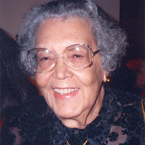 A medium skin-toned older woman with short gray hair smiles at the viewer. She wears clear-framed glasses and a black, floral patterned shirt.
