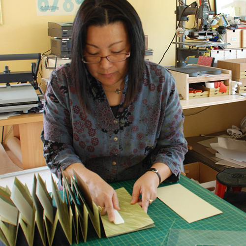 A light-medium-skinned adult woman with medium-length black hair wears a blue floral blouse and glasses. She is in an art studio, behind a green cutting mat, looking down and holding open a flag-style book. Equipment is on the counter behind her.
