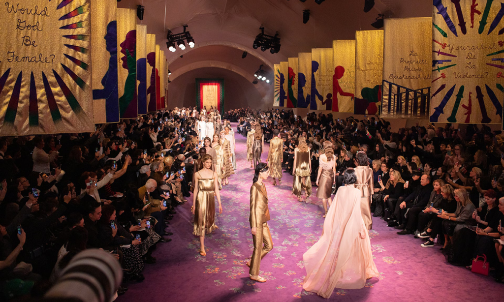 Models walk the final act of Dior's couture show against Judy Chicago's backdrop of embroidered feminist banners.