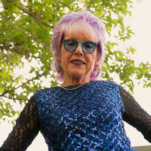 A light-skinned older woman with short purple-and-white hair smiles slightly, arms out to the side. She wears a blue sequin top with long black lace sleeves, a gold necklace, hoop earrings, and blue glasses. The sky and tree branches are behind her.