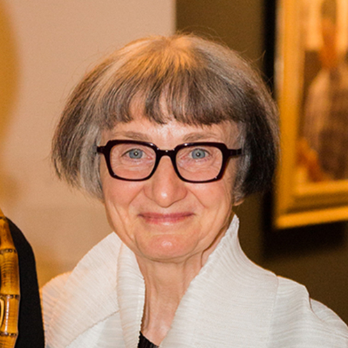 A light-skinned older woman with dark hair streaked with gray, cut in a short bob. She wears a white, high-colored top. She smiles as her blue-gray eyes gaze directly at the camera from behind eyeglasses with a thick, dark frame.