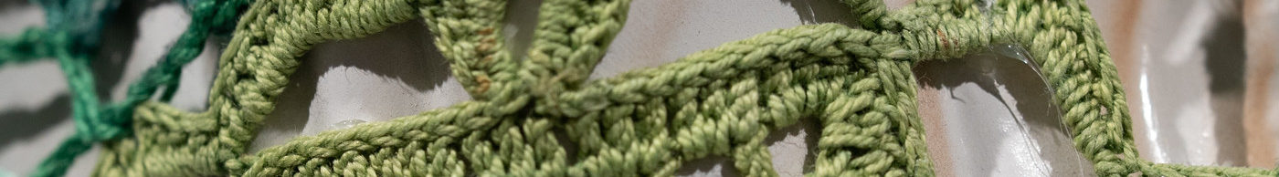 Close-up detail of a larger artwork shows the closeup detail of an off-white ceramic surface that is covered by panels of crocheted yarn in emerald and citron green.