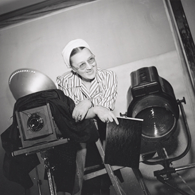 Black-and-white photo of a light-skinned adult woman leaning out from behind a large studio camera. Wearing glasses, a white turban and a stripped top, she smiles with an expression of humor. A large spotlight sits behind her and she holds a piece of large format film.