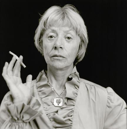 A black-and-white photograph of a light-skinned older woman. She has closed cropped light hair and is shown from the chest up. She wears a long sleeved shirt with a ruffled collar and sleeves and a large silver necklace. In one hand she holds a lit cigarette.