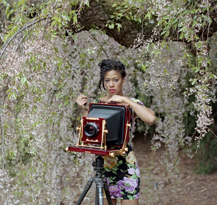 Artist Deana Lawson stands in front of a wisteria tree, behind an old camera, and holds the shutter click; she stares seriously at the viewer and is wearing a floral dress that compliments the tree.