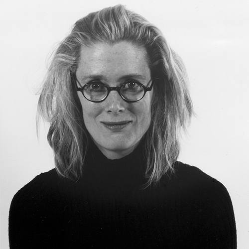 Black-and-white studio portrait of a smiling light-skinned adult woman with medium-length blond hair. She wears round glasses and a black turtleneck sweater.