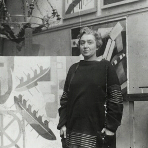 A black-and-white photograph of a light-skinned, adult woman standing in her studio and surrounded by her large, abstract, geometric paintings. Her hair is short, light, and curly, and her hands rest in the pockets of the loosely fitted, dark colored, long-sleeved dress she is wearing.
