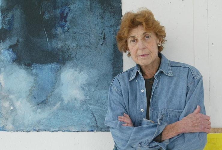 A light-skinned older woman with short, wavy, red hair and brown eyes stands with her arms crossed. She leans against a white wall with part of a blue abstract painting behind her. She wears round silver-color earrings and a blue demin long-sleeve button-up shirt.