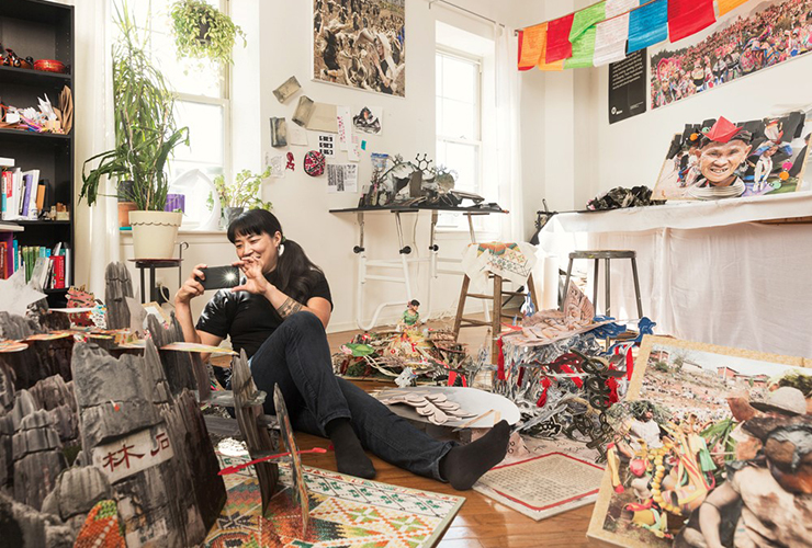 A light-skinned, adult, Asian woman with black hair dressed in black sits on the floor of her cluttered studio surrounded by elaborate pop-up books. She holds up her mobile phone to take a photo.